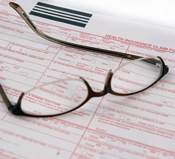 Eyeglasses on top of health insurance form